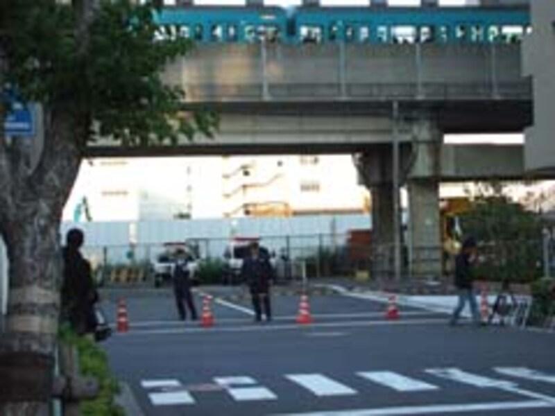 江東区潮見の事件現場マンション前。警察官が立ち、マスコミも並ぶ