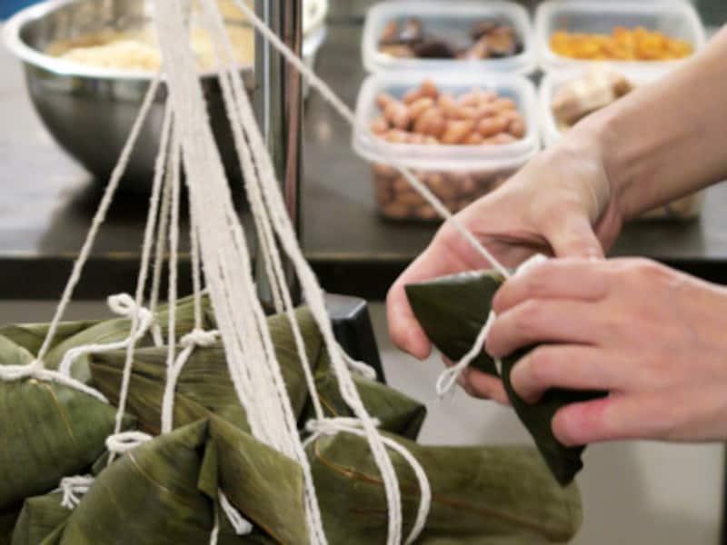 しょう油味のもち米、4種の具材を2枚の笹の葉で包み、三角に折ってひもで結びます。一つひとつ、丁寧に手作りされています(2015年10月9日撮影)