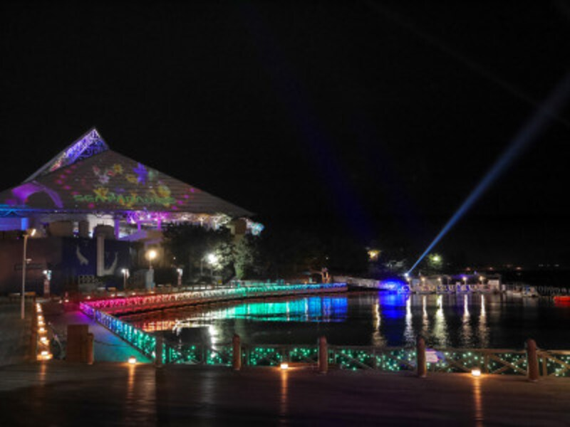 イルミネーションが水面に反射する「シーサイド・プロムナード」と三角屋根に映し出されるプロジェクションマッピング「スカイライトマジック」(2018年11月8日撮影)