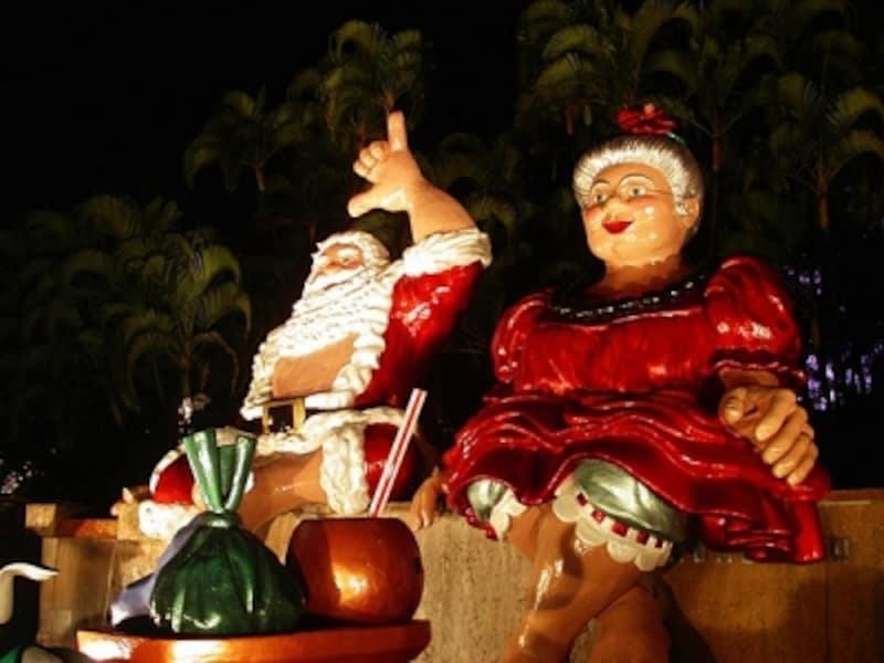 ハワイのサンタクロース夫妻は、衣装も南国バージョン。夫人の髪にはハイビスカス、腕にはハワイアンジュエリーも