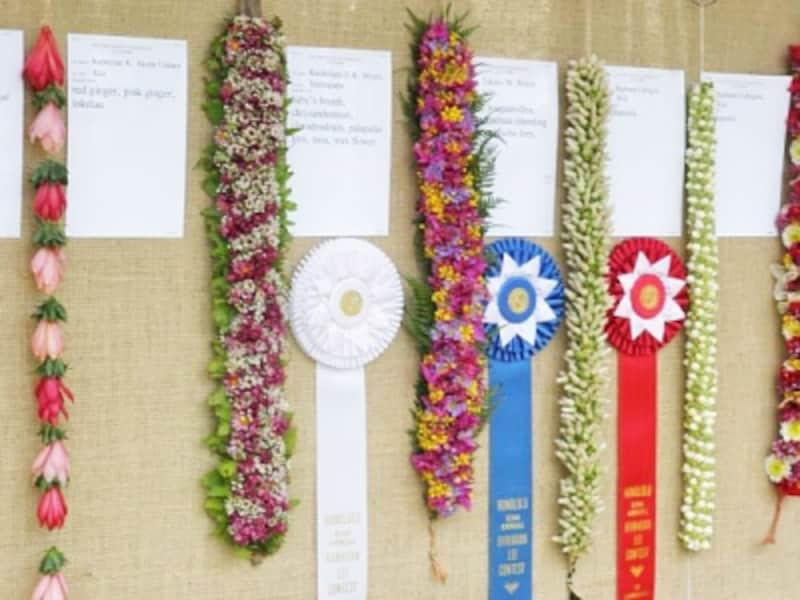 いくつもの花や葉、木の実を糸で通し、結び、編み込んで作られる花束のようなレイ