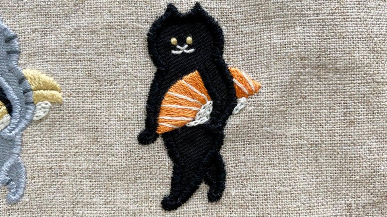 サーモンの握り寿司をかっこよく持ち運ぶ猫の刺繍に「こういうのめっちゃ好きです」「このしたり顔よw」と絶賛の声