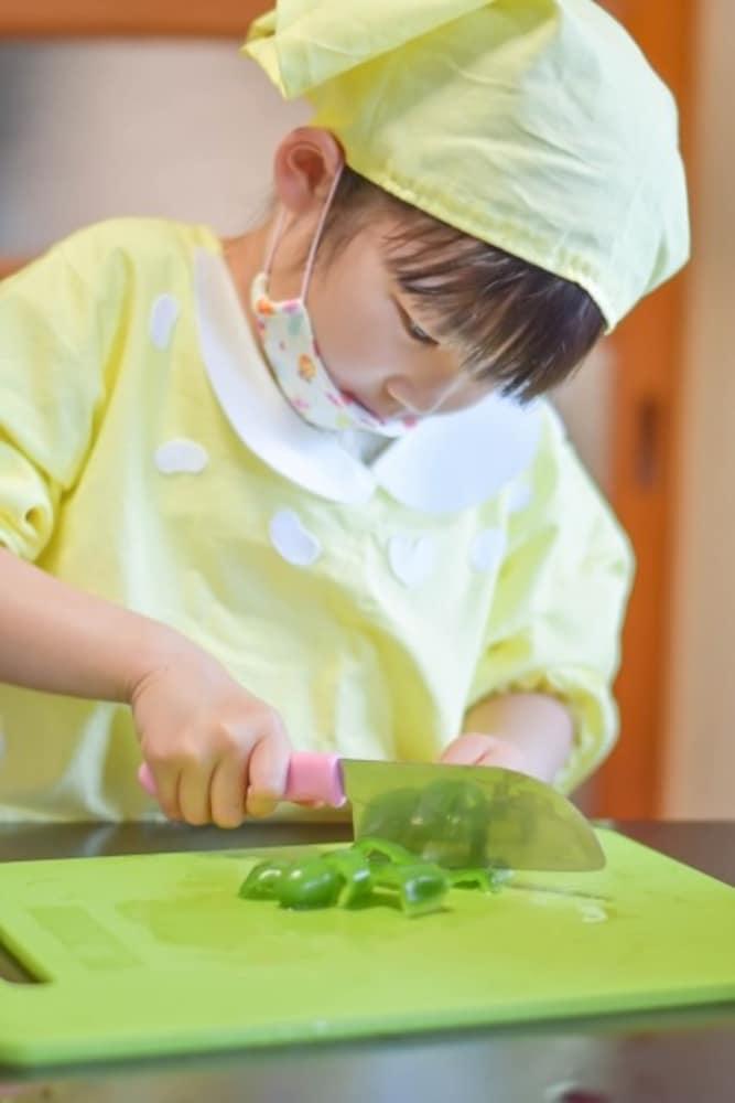 包丁で野菜を切る子供