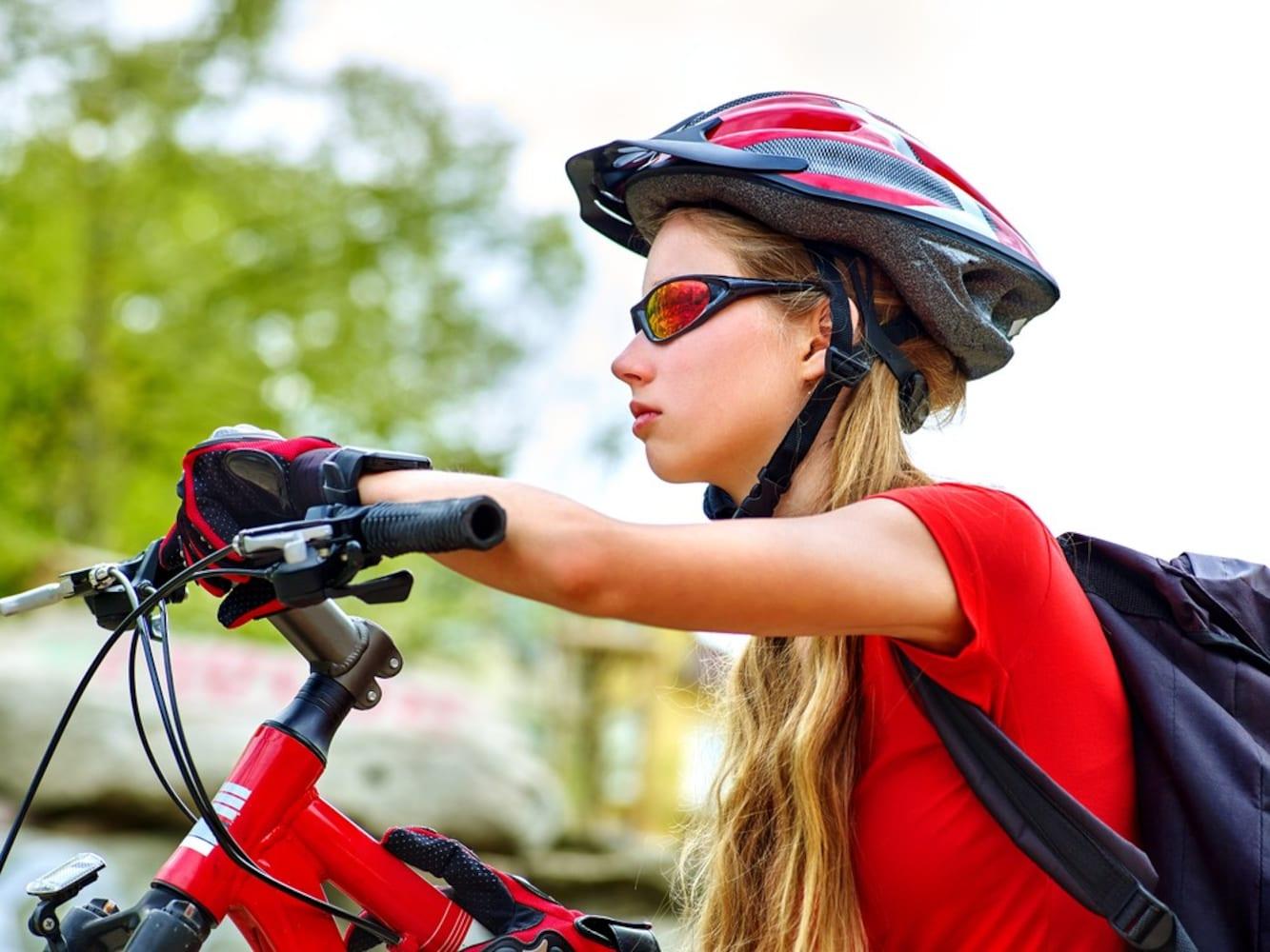 ヘルメットを着用してクロスバイクに乗る女性