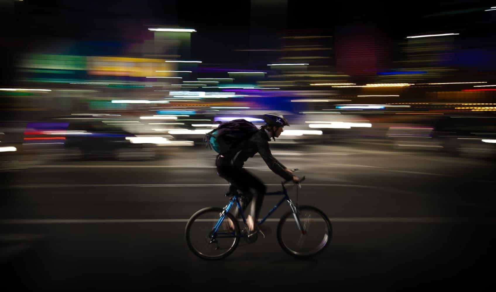 夜の街をロードバイクで走る男性