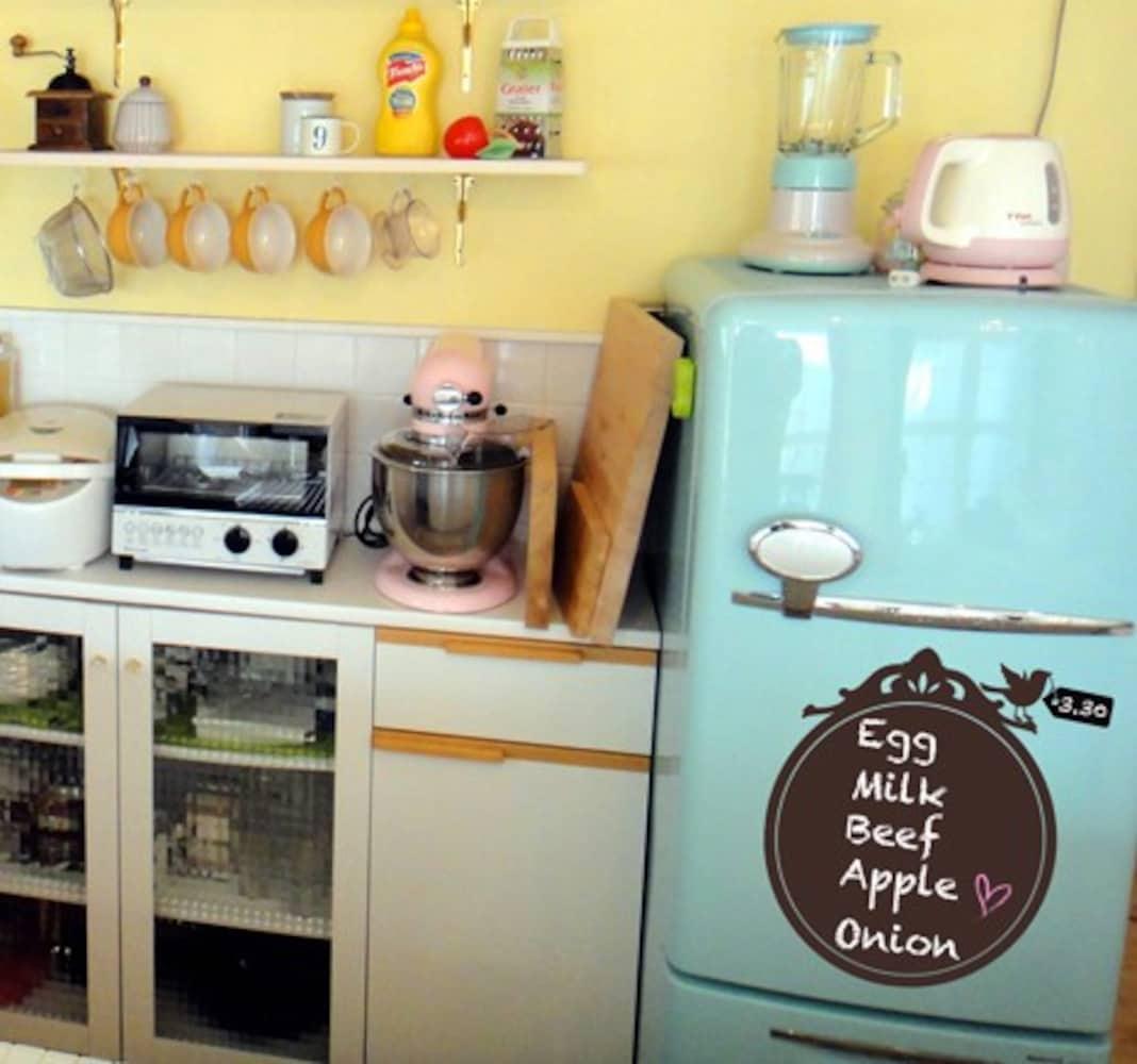 ミニ黒板を張り付けた冷蔵庫とキッチン周り