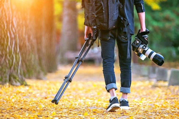 三脚とカメラを持つ男性