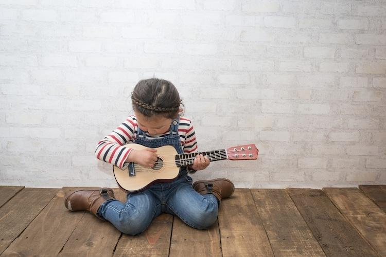 1人でギターを弾く少女