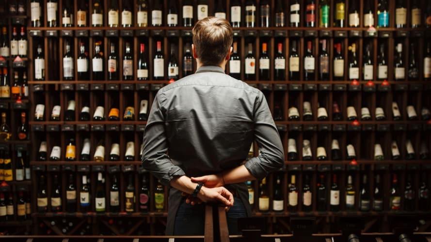 ワイン棚を眺める男性
