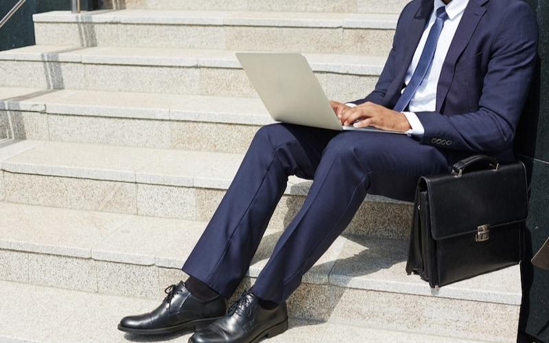 ビジネスバッグを床に置いて作業をする男性
