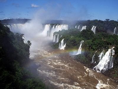 ブラジル側から見たイグアスの滝のハイライト、悪魔の喉笛。酸化鉄からなるラテライトが混ざり込んだ赤い水の流れ、濃い青空に舞い上がるまっ白な水煙、そして7色の虹 ©牧哲雄