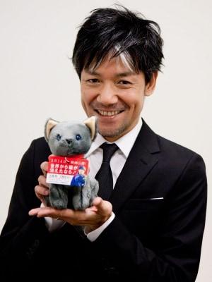 永井監督、キャベツ君の縫いぐるみを抱いてにっこり