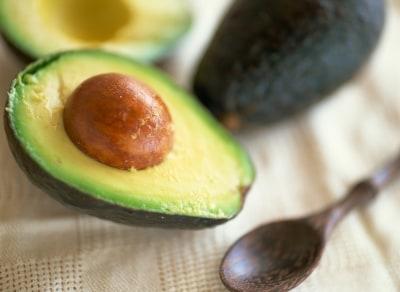 アボカドごつごつとした皮の中身は、きれいなクリームイエローの果実と大きな種です