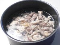 鍋にもつ、だし、生姜、酒を入れて煮る