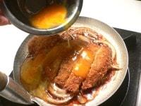 たまねぎが煮えたらとんかつをのせ、すぐに溶き卵を流す