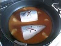 調味液にさばと生姜を入れ、火にかける