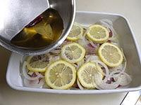 バットにたまねぎ、いわし、レモンを入れ、浸け液を回しかける