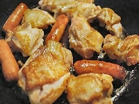 フライパンで鶏肉とウィンナーを焼く