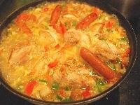 米を炒め、トマトと水、調味料、肉を加える