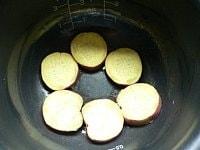 内釜にバターをぬって芋を敷く