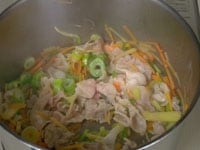 サラダ油で豚肉と野菜を炒める