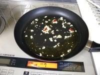 オリーブオイルとニンニクを炒め、赤唐辛子を炒める