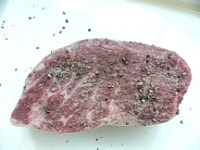 肉を室温に戻し、ニンニクをこすりつけ、塩コショウする