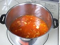 トマトジュースと水を加え、煮る