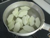冬瓜を切り、水に入れて茹でる