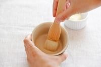 にんにくとバターを容器に塗る