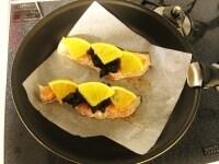 鮭の上にオレンジとプルーンをのせ蒸し焼きにする
