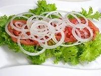 お皿にレタス、トマト、玉ねぎをのせる