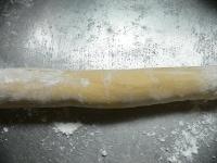 打ち粉を敷いた台の上で、生地を転がして伸ばして輪にする