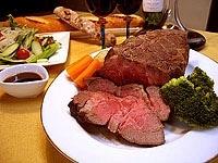 タコ糸を取り除いた肉を切り分け、ソースと野菜を添える